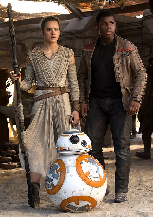 "Rey turned to the droid. ""What is it?"" She looked up, past the now concerned Finn. ""Over there?"" Trailing her gaze, he was able to make out in the distance the hulking forms of the two thugs who had attacked the girl and tried to steal the droid. They were not alone. The sun gleamed off the bright white armor of two stormtroopers. One of the banged-up hooligans was pointing in Finn's direction."