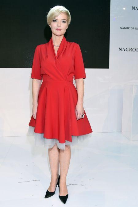 Monika Zamachowska ubrana w czerwoną sukienkę rozkloszowaną, delikatny, srebrny naszyjnik i czarne szpilki.