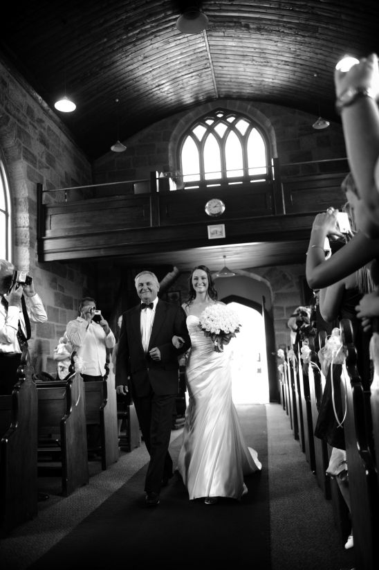 The wedding ceremony photo inside the Holy Cross Church at Kincumber was full of emotion the moment the father and the bride walked down the aisle. Wedding Photography on the Central Coast by Impact Images  - www.impact-images.com.au