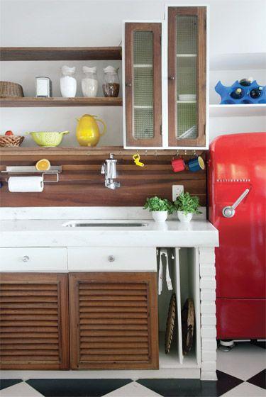 Poucos armários fechados e muitas prateleiras, na cozinha integrada, deixam à mostra utensílios graciosos, que a designer de interiores encontra com seu olhar treinado.