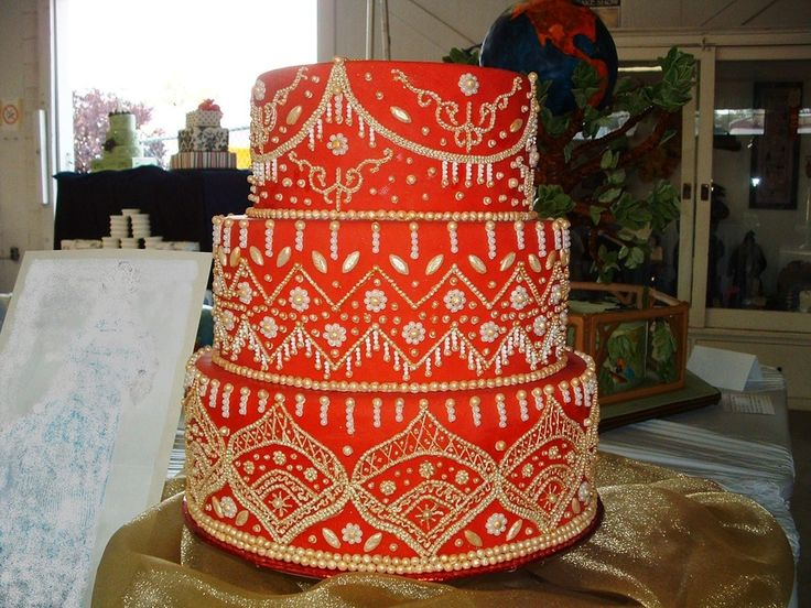 The theme for the wedding cakes was the wedding dress.  I designed a cake after a lehenga gown.  12-10-8 tiers covered in red fondant and approximately 9,000 sugar beads painted with edible gold glaze and gold petal dust.  This was the hardest wedding cake Ive ever done.  I was very happy with the end result and ended up winning first place in the intermediate division.  Happy looking!!