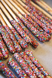 Dip grissini sticks in melted chocolate and then sprinkle on 100's and 1000's.