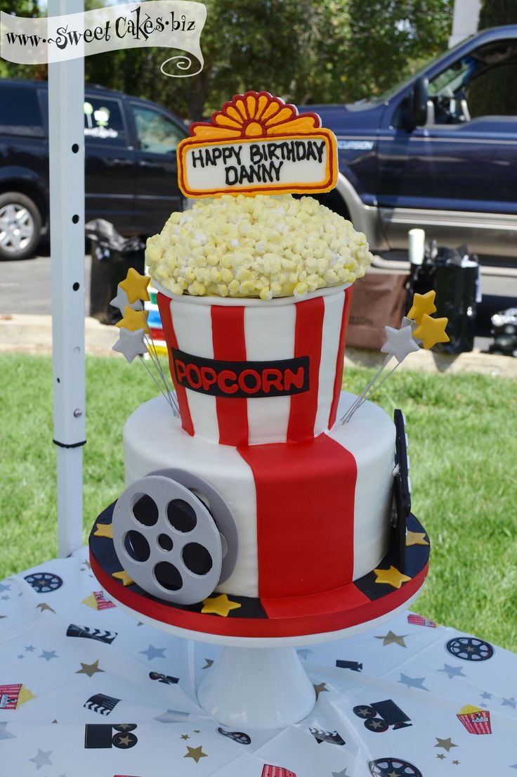 """2 tier hollywood themed cake with a rice cereal fim reel, a director's board, movie marque happy birthday and giant bucket of """"popcorn"""""""