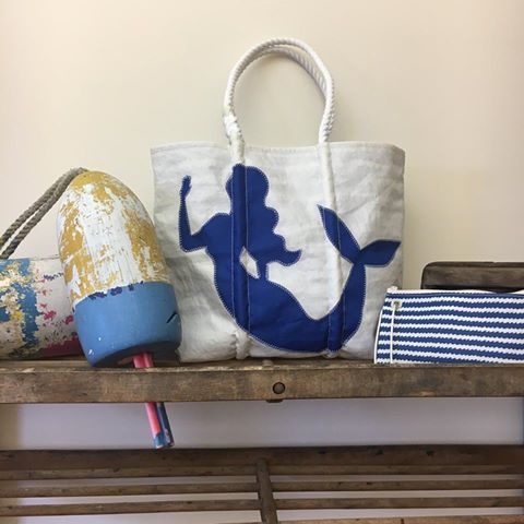 Tales of mermaids have been around as long as sailors have braved the high seas. Depicted here in royal blue applique on recycled sail cloth, this mermaid silhouette beckons with a wave of her hand. The interior of the bag is lined with a bright blue wave print designed to make a visual splash.