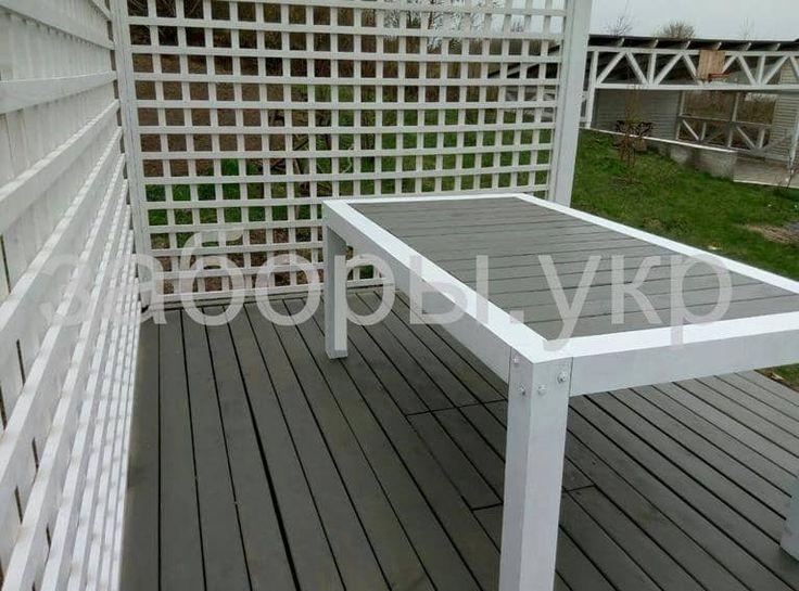 Белая открытая терраса - пергола с деревянным столом из дерева