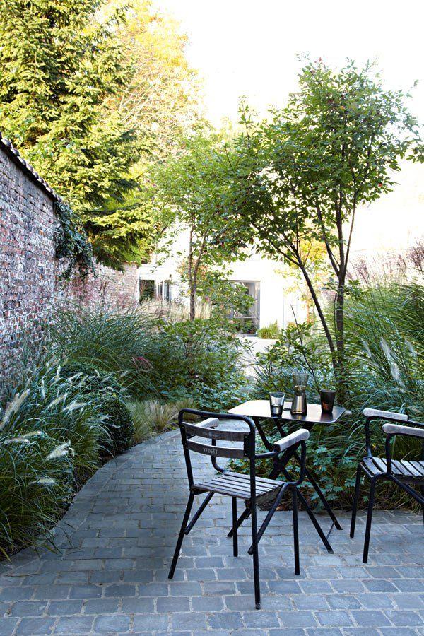 Imaginé par le paysagiste Dominique Lievrouw (Timber Management), ce jardin sauvage orné de roseaux, est traversé par un chemin pavé Une maison au design scandinave des années 50 - Marie Claire Maison