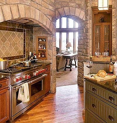 Cook's Center    The gas range has an alcove of its own surrounded by cultured stone. Narrow, built-in shelves on either side of the range are perfect for storing spices.
