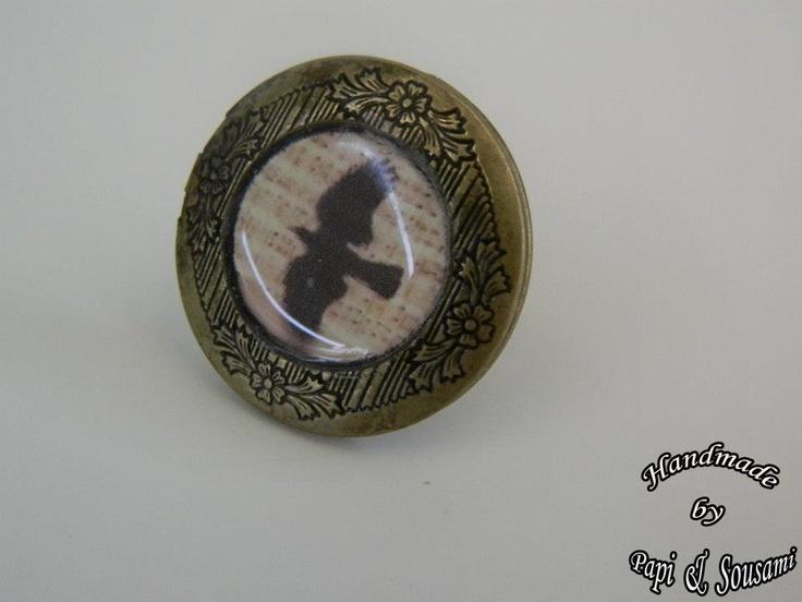 Στρογγυλό δαχτυλίδι ρητίνης σε μπρούτζινο πλαίσιο με κοράκι σε παρτιρούρα, που ανοίγει για να βάλετε αγαπημένα memorabilia μέσα του- Round bronze tone photo frame locket resin ring with a partiture and a raven