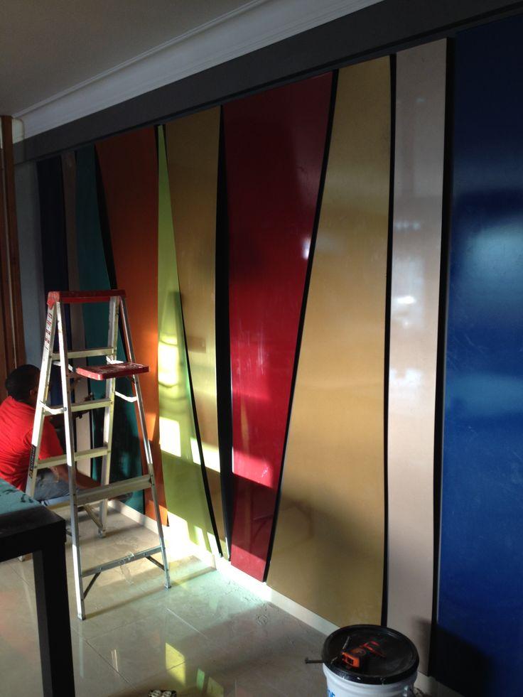 Torre CG6. Diseno en la pared con elementos metalicos,pintados con pintura automotriz en colores perlados y metalicos , desde el nivel del zocalo casi hasta la viga.