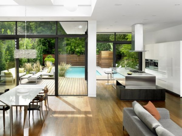 Open plan kitchen living room leading through large glass doors to a small garden with a pool