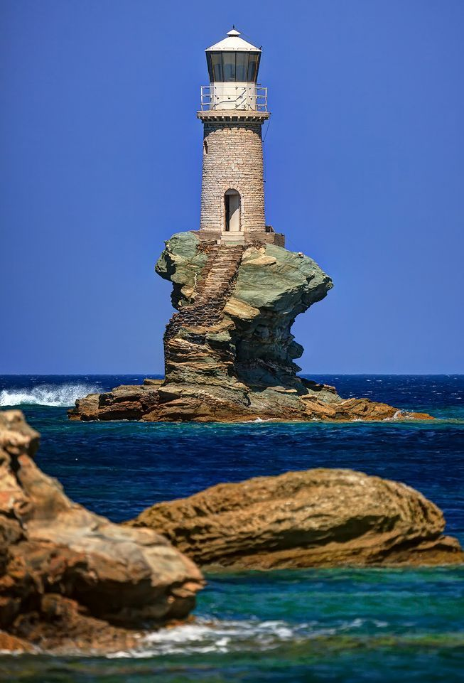 Rising from a precarious chunk of sea rock off the coast of Andros, Greece, the Tourlitis Lighthouse is so whimsical and surreal that it almost looks Photoshopped.
