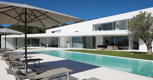 Located on the west coast of Ibiza, Villa Ixos offers some of the best views of the city and the bay, perfect for any vacation. The sunset-facing villa, designed by Belgian architect Bruno Erpicum, is located on 4 acres in the middle of a pine forest surrounded by orange and olive trees.