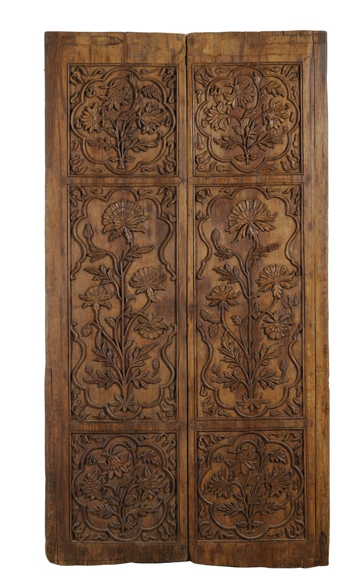 A PAIR OF MUGHAL CARVED WOODEN DOORS, INDIA, 17TH CENTURY comprising two wooden doors, each of rectangular form divided into three panels finely carved with flowering plants within lobed cartouches, the spandrels filled with cloud motifs, affixed at the back, reverse plain