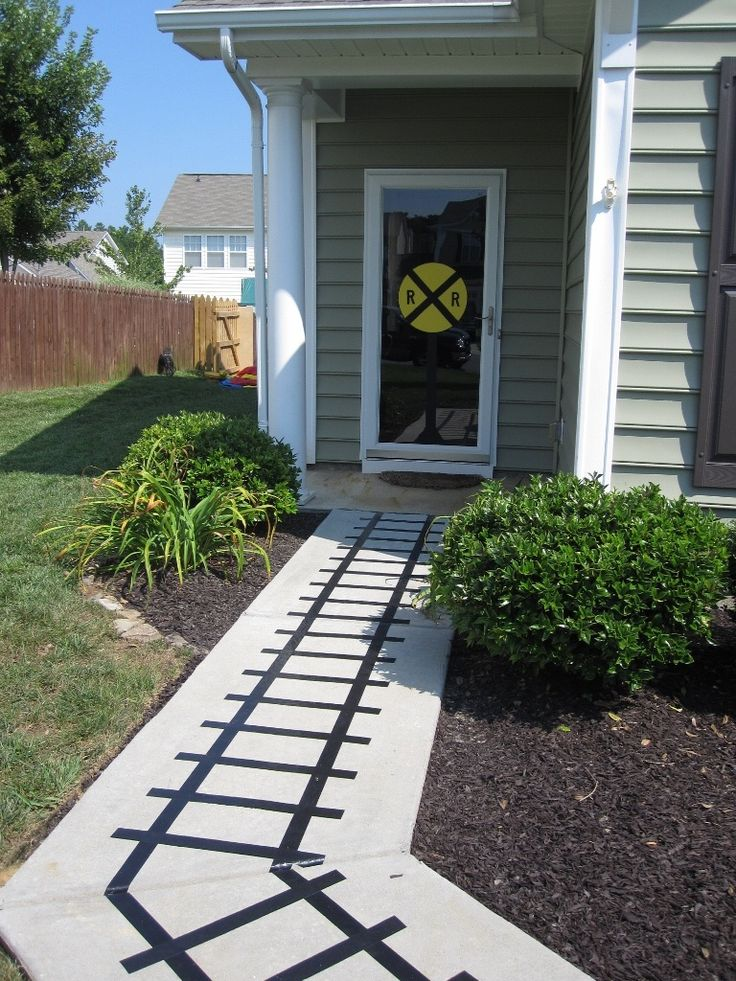 Train track along walkway-love it! Just tape with electrical tape  voila! The Railroad crossing sign on the front door is perfect too.