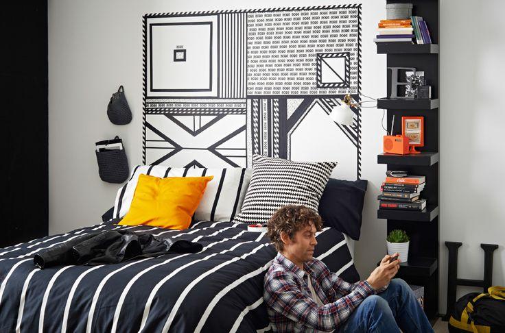Camera da letto con testiera realizzata con nastri adesivi bianchi e neri applicati alla parete. Copripiumino TUVBRÄCKA bianco e nero. Cuscino STOCKHOLM arancione.