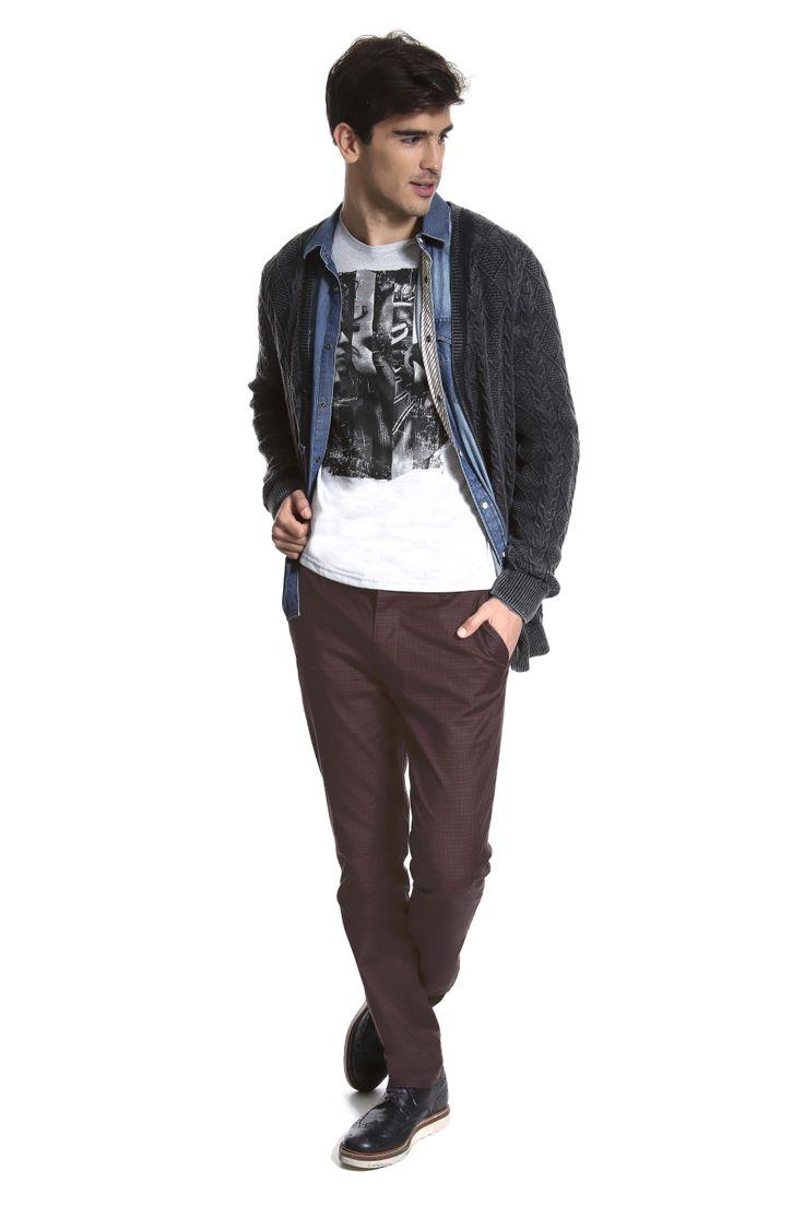 T-shirt estampada sobreposta por camisa jeans e casaco de tricô lavado. A calça é marrom xadrez.
