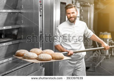Handsome baker in uniform taking out with shovel freshly baked buckweat bread from the oven at the manufacturing - stock photo