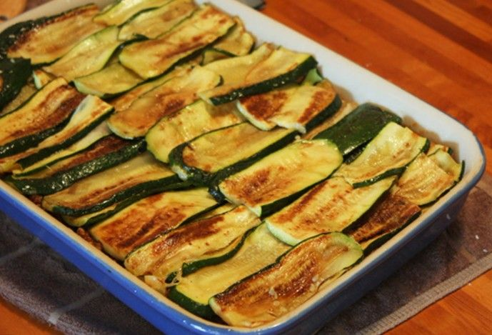 Moussaka+med+ristet+squash+(4+portioner+a`269+kcal.)    2+løg 2+fed+hvidløg 550+g+hakket+magert+oksekød 1+glas+økologisk+tomat+med+grønsager 2+auberginer+(550+g) 3+squash+(650+g) salt,+peber+og+kanel. økologisk+bouillon  Kødsauce: