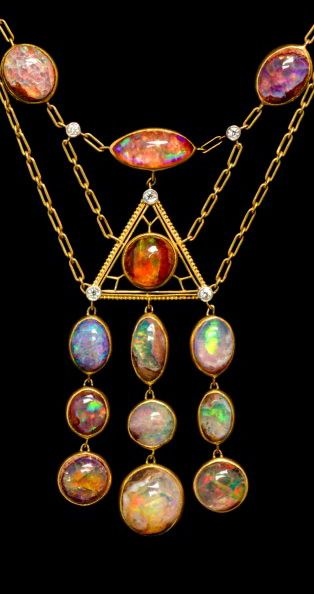 An Arts and Crafts Yellow Gold, Platinum, Opal and Diamond Necklace, Tiffany & Co., Circa 1910, consisting of 17 oval and navette shape cabochon cut bezel set boulder and fire opals of nearly colorless to orange body color, exhibiting strong play-of-color and measuring from approximately 12.85 x 5.45 mm to 11.60 x 11.00 mm, the opals set surrounding and within an intricately textured open wirework center in an equilateral triangle shape, the center section supporting a three row tassel of…