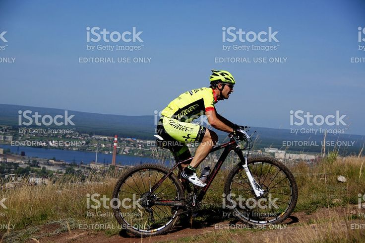 Upper Ufaley, Russia - August 10, 2014: Racer mountain bike uphill against sky during cross-country marathon 'Big stone 2014'
