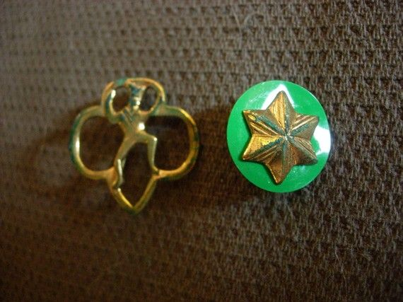 Girl Scouts Brownies membership pin and star pin. I still have my star with the green backing, even though I was only in Girl Scouts for a year. Went to camp, though!