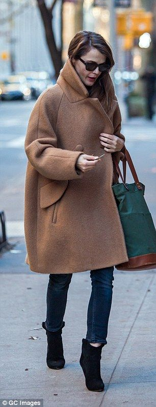 Heading home: She carried her large green material bag with brown leather strap over her l...