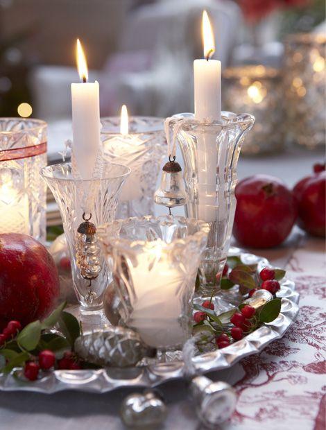 Strahlender Mittelpunkt: Kerzenlicht und funkelndes Kristall gehen immer eine gelungene Verbindung ein. Schön festlich wirken Vasen in unterschiedlichen Größen auf einem Silbertablett, das mit Baumanhängern, Beeren und Granatäpfeln geschmückt ist (Foto: FloraDeko)
