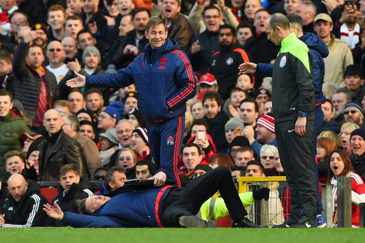 Manchester United's Dutch manager Louis van Gaal falls over on the touchline in front of fourth official Mike Dean and Arsenal's French manager Arsene Wenger during the English Premier League football match between Manchester United and Arsenal at Old Trafford in Manchester in north west England on February 28, 2016.