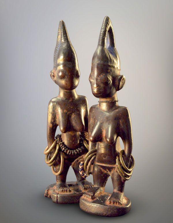 Paire de jumelles Ibeji, Yoruba, Nigeria, fin du XIXe-début du XXe siècle. Bois sculpté à l'herminette, bracelets en bronze et ceinture de perles. H. : 22 cm. © Galerie Noir d'Ivoire, photo : Modandwa