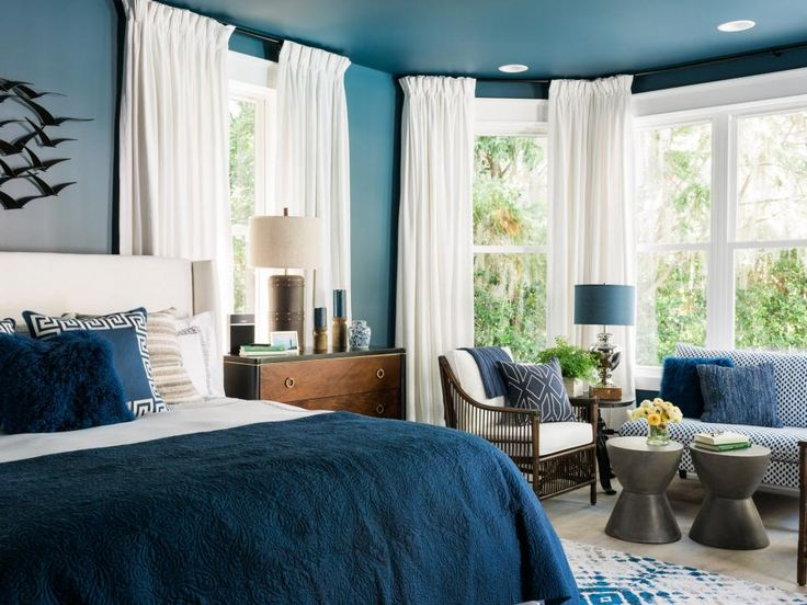 Rich navy blue walls with crisp white accents and a global influence creates a captivating master bedroom with beautiful views and designated spaces for rest and relaxation.