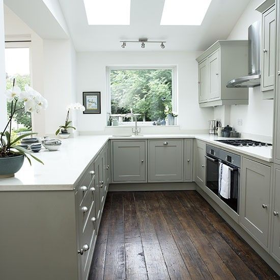 Dark wooden flooring provides a dramatic contrast to the pale kitchen cabinets.