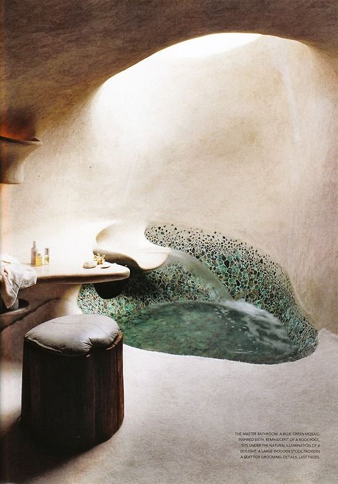 The master bathroom. A blue-green mosaic-inspired bath, reminiscent of a rock pool, sits under the natural illumination of a skylight. A large wooden stool provides a seat for grooming.