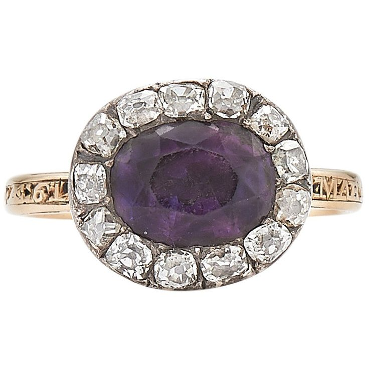 An oval amethyst is set to the center of an old mine diamond cluster with a total of approximately 0.75cts mounted in silver topped yellow gold. The memorial ring is well worn for Mary, 1770, with another illegible inscription. The shank would have originally been enameled black.