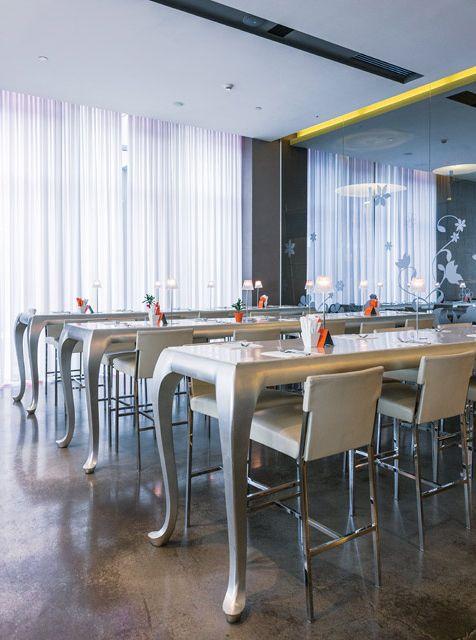Comedor del hotel Nhow Milano con mesas altas de prominentes patas torneadas (Matteo Thun) y pared espejada. El piso es gris y los ventanales tienen cortinas blancas.