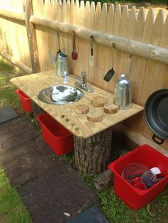 I love the use of the tree stump legs and wooden hob rigs on this mud kitchen.