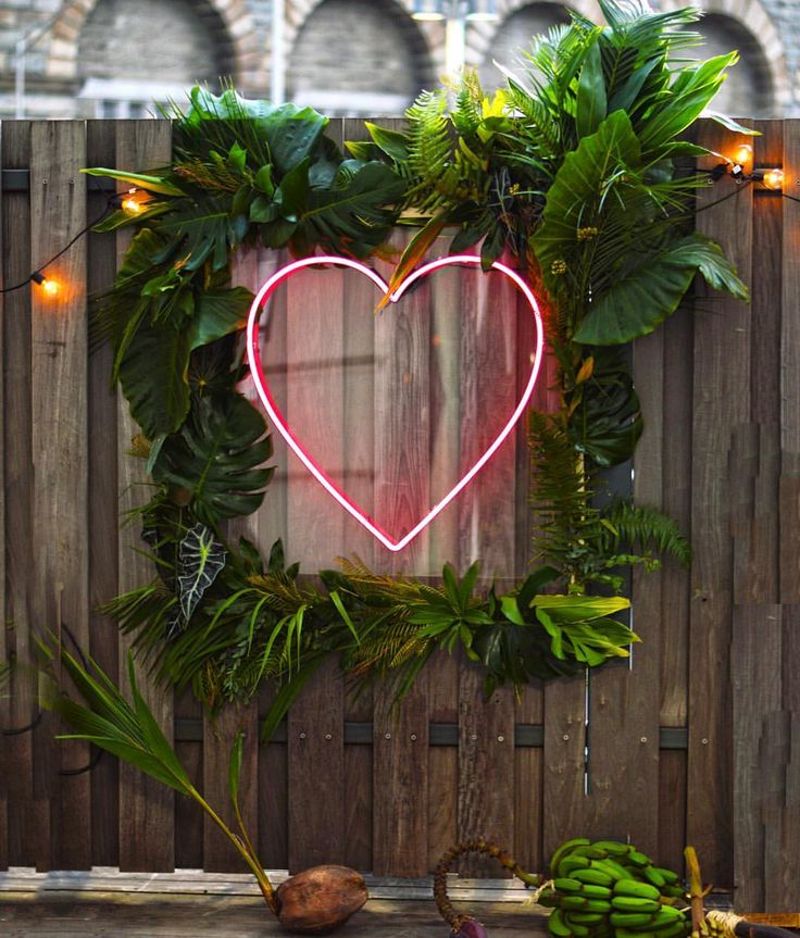 Tropical backdrop with green leaves and neon heart by @tincanstudios in Brooklyn