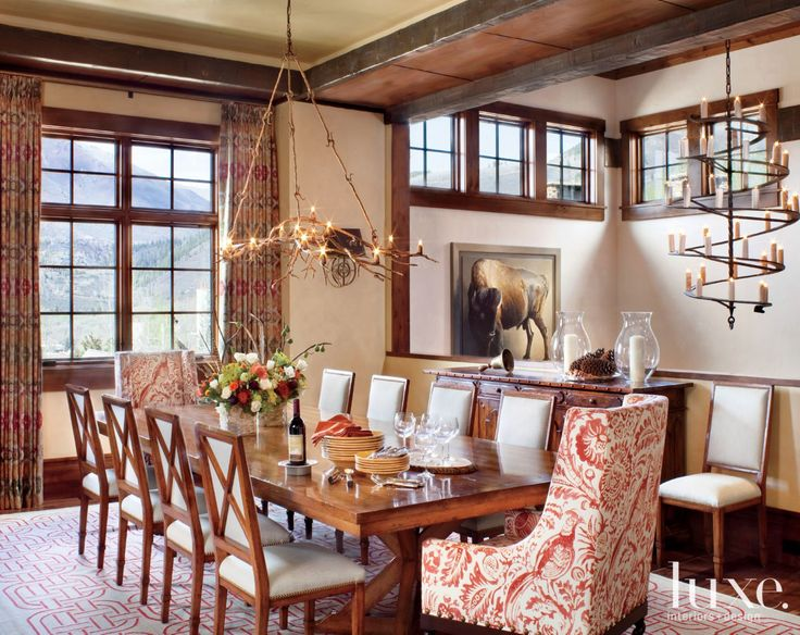 Clean-lined X-backed dining chairs face a custom table, all by Bausman & Company, in the dining room. The branch chandelier by Paul Ferrante lends an outdoor feel, while host  and hostess chairs from Studio 534 in Boston are upholstered in a Clarence House textile.