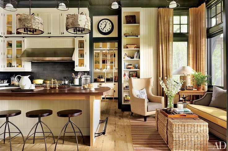 Country breakfasts are served in the Thom Filicia–designed Adirondack vacation home of a California couple. The kitchen's barstools are by Marsia Holzer Studio, and the wing chair at right is from Lillian August.