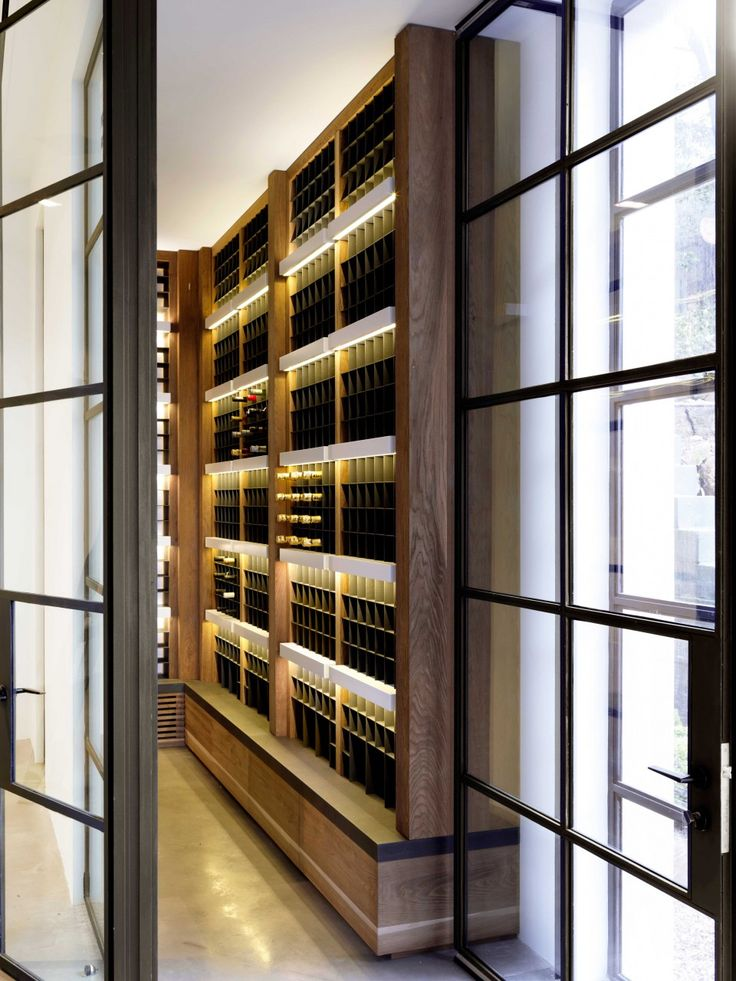 This custom wine cellar is gorgeous! I love the black details in the panes of the window paired with soft ambient casegood lighting.