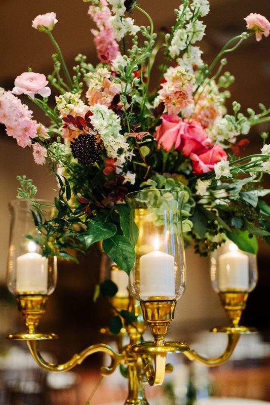 tall brass candleabra centerpieces were highlighted by a an overflowing large arrangement of rich summer flowers including antique hydrangea, pink and white larkspur, pink roses, pink ranunculus, peach stock, ruskus, crepe myrtle and burgundy scabiosa.