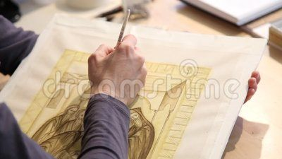 Icon painting - paintbrush in the right hand and her left hand underneath.