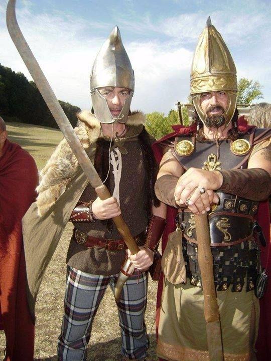Dacian reenactors, both wielding a falx, a long, sickle-shaped weapon dreaded by Roman legionaries.