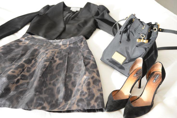 Chaqueta torera, falda con print animal, stilettos y bolso en negro.