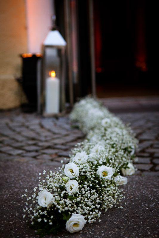 Eine wunderschöne Girlande aus Grün, Schleierkraut und kleinen weißen Rosen, die bei dieser Hochzeit nach der Trauung vor den Eingang gelegt wurde, um diesen zu säumen.  Fotografie: http://www.annalenazintel.de/ http://www.festefeiern.by/