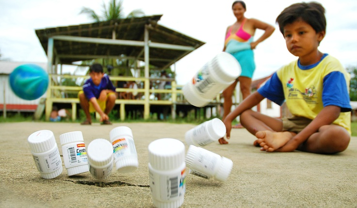 Kids in a village along the Amazon River bowling with a small toy ball and empty vitamin containers. (the containers were brought along with this Mission Trip) | #photojournalism #kids #games #candid #Brazil #Amazon | www.brandonjpro.com