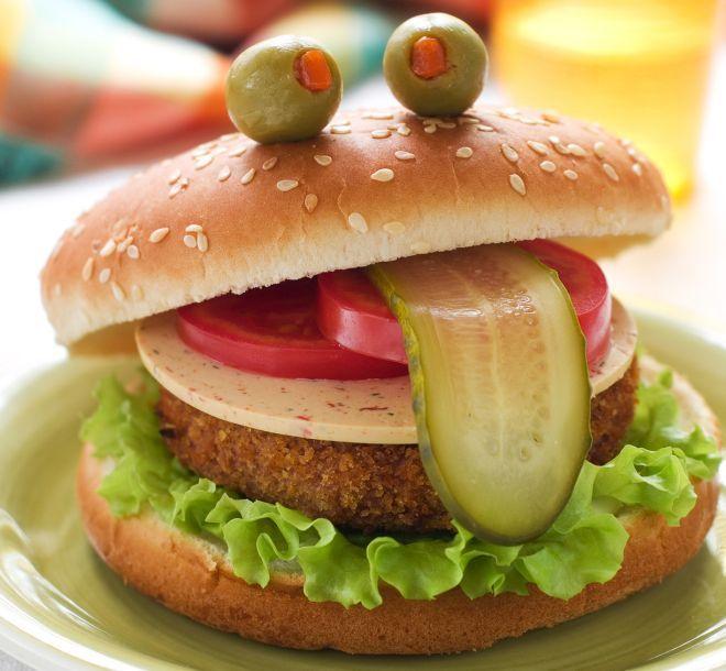 Per il buffet di Halloween una bella ricetta sana, persino vegetariana: un panino composto da un burger di verdure, reso divertente da qualche verdurina che piace ai bambini. Ingredienti: una patata, una carota, un cucchiaio di piselli, un uovo, parmigiano, sale, pangrattato, formaggio a fette, maionese e ketchup, pomodori, zucchine grigliate, lattuga, olive ripiene. Prepariamo la polpetta vegetale: lessiamo la patata e la carota, aggiungiamo i piselli, scoliamo bene. Schiacciamo la patata…
