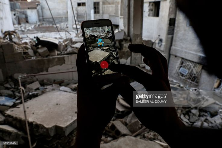 TOPSHOT - A Syrian gamer uses the Pokemon Go application on his mobile to catch a Pokemon amidst the rubble in the besieged rebel-controlled town of Douma, a flashpoint east of the capital Damascus on July 23, 2016. / AFP / Sameer Al-Doumy        (Photo credit should read SAMEER AL-DOUMY/AFP/Getty Images)