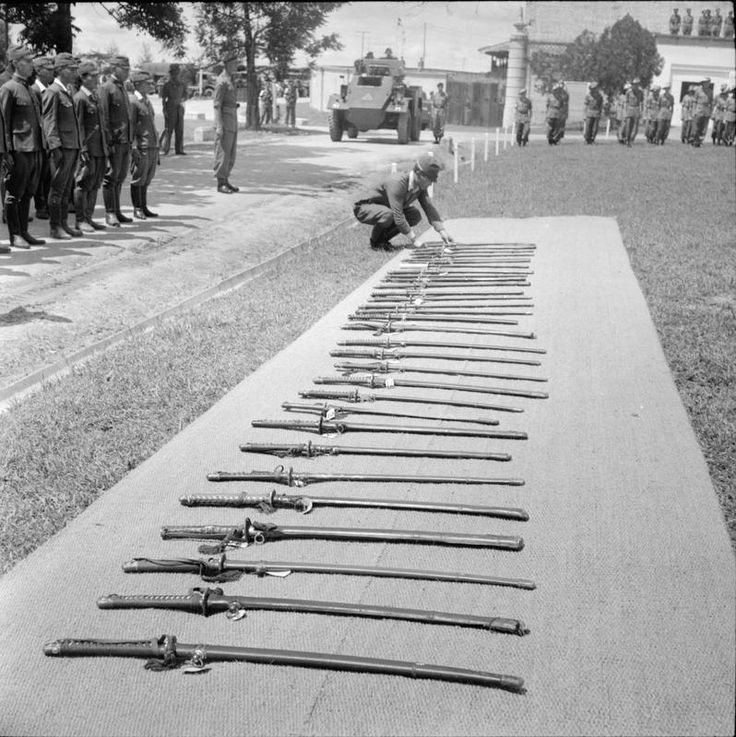 A Japanese officer from the 7 Area Army Headquarters lays his sword beside those of his fellow officers at an official ceremony of surrender presided over by Major General C G G Nicholson CB, CBE, DSO, MC, of the British 2nd Division, at Johore Bahru, Malaya. In all 37 Japanese officers, mostly from the 7 Area Army Headquarters, handed over their swords.