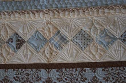 """I love how she quilting the triangles, although I think you could only do this is smaller (say 6"""") setting triangles like the one shown.  It's a nice sharp linear design when I've been looking at more curvy designs for my current projects.  Must remember this."""
