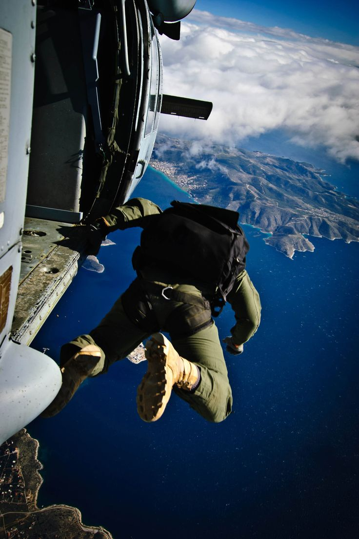 """A Sailor assigned to Naval Special Warfare, U.S. Special Boat Team, jumps out of the MH-60S Sea Hawk helicopter """"Ghostrider 53"""", assigned to Helicopter Sea Combat Squadron (HSC) 28, Det. 1, as it flies over Megara Army Airfield as during the final day of a multi-week joint exercise."""